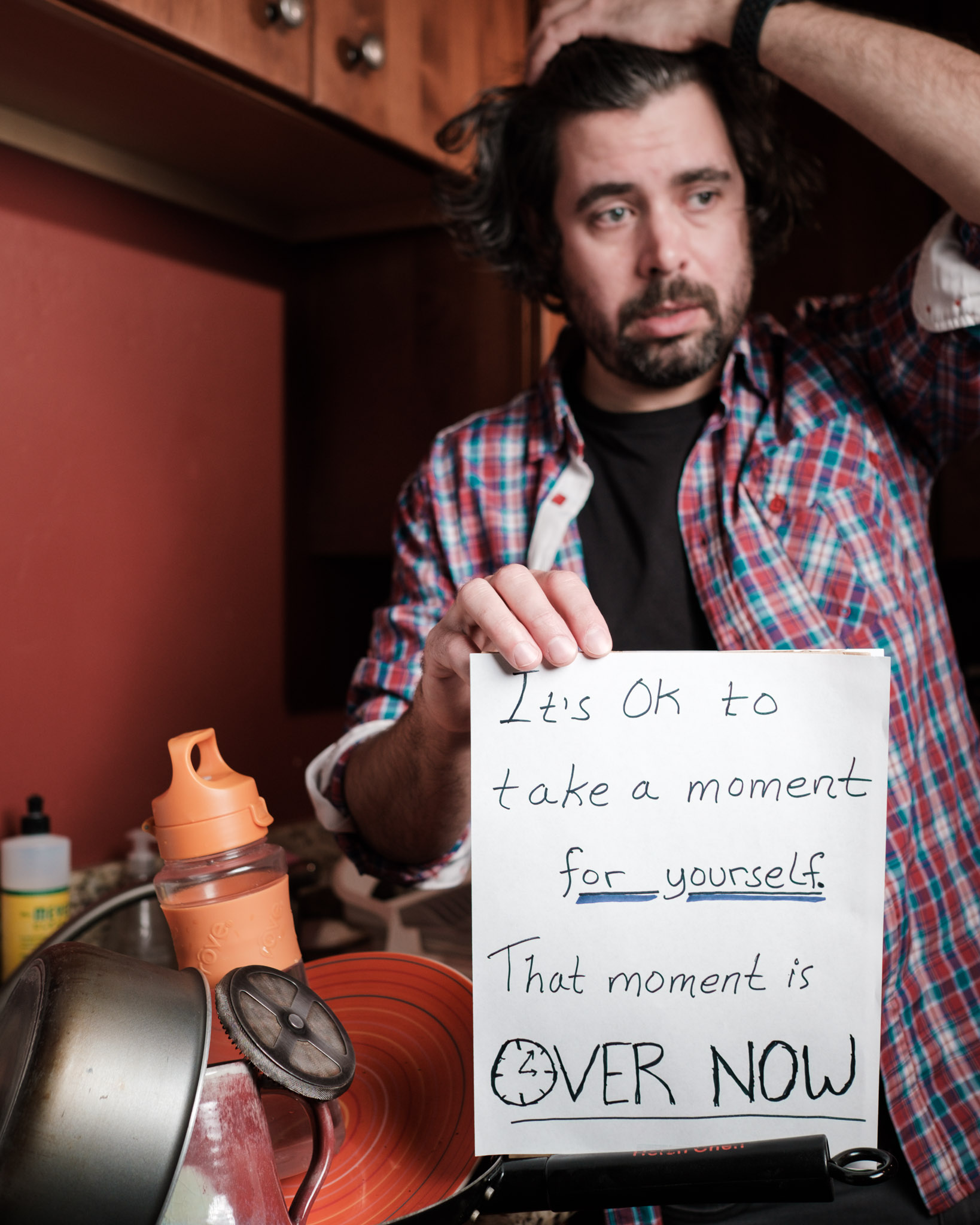 Photo of Daven in kitchen with pile of dirty dishes holding sign that reads
